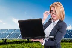 Donna di affari con la centrale elettrica solare nel fondo Fotografia Stock