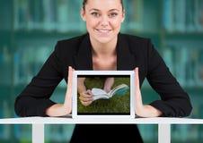 Donna di affari con la compressa che mostra libro su erba contro lo scaffale per libri confuso con la sovrapposizione dell'alzavo Fotografia Stock Libera da Diritti