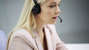 Donna di affari con la conversazione della cuffia avricolare e del computer video d archivio