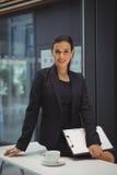 Donna di affari con la lavagna per appunti che si siede sullo scrittorio all'ufficio Immagini Stock