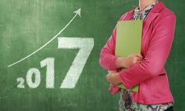 Donna di affari con la lavagna per appunti che sta accanto ai numeri 2017 Fotografia Stock