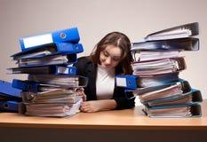 Donna di affari con la pila di cartelle all'ufficio Fotografia Stock