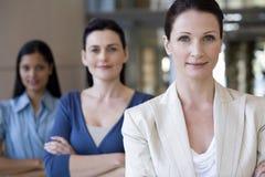 Donna di affari con la squadra dietro Immagine Stock Libera da Diritti