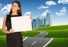 Donna di affari con la strada che conduce al centro di affari Immagini Stock