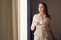 Donna di affari con la tazza di tè che guarda attraverso la finestra dell'ufficio Immagini Stock