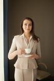 Donna di affari con la tazza di tè che guarda attraverso la finestra dell'ufficio Fotografie Stock