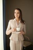 Donna di affari con la tazza di tè che guarda attraverso la finestra dell'ufficio Immagine Stock Libera da Diritti