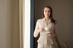 Donna di affari con la tazza di tè che guarda attraverso la finestra dell'ufficio Fotografia Stock Libera da Diritti