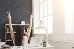 Donna di affari con le mani sollevate in ufficio, vista posteriore Fotografia Stock