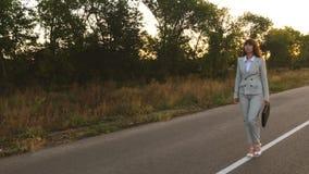 Donna di affari con le passeggiate nere della cartella sull'asfalto con le marcature bianche stock footage