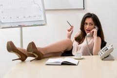 Donna di affari con le sue gambe sulla tavola Fotografia Stock Libera da Diritti