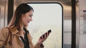 Donna di affari con lo smartphone in automobile di sottopassaggio Pendolare femminile abbastanza giovane che usando messaggero ap video d archivio