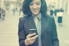 Donna di affari con lo smartphone che cammina sulla via telefono a fuoco Fotografia Stock