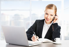 Donna di affari con un computer portatile e un telefono del computer Fotografia Stock
