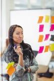 Donna di affari creativa che esamina le multi note appiccicose colorate Immagini Stock Libere da Diritti