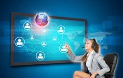 Donna di affari in cuffia avricolare facendo uso del touch screen Fotografia Stock