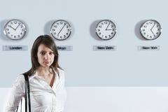 Donna di affari davanti agli orologi della fascia oraria del mondo Fotografia Stock Libera da Diritti