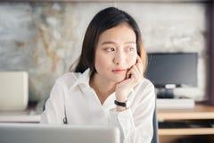 Donna di affari degli asiatici della nuova generazione che per mezzo del computer portatile all'ufficio Immagine Stock Libera da Diritti