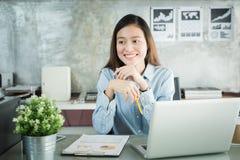 Donna di affari degli asiatici della nuova generazione che per mezzo del computer portatile all'ufficio, Asia Immagine Stock