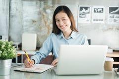 Donna di affari degli asiatici della nuova generazione che per mezzo del computer portatile all'ufficio, Asia Fotografie Stock