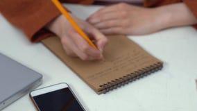 Donna di affari del primo piano che scrive le note in taccuino Donna sul posto di lavoro archivi video