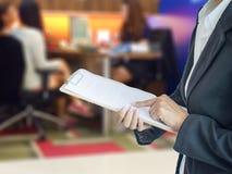 Donna di affari dell'Asia che analizza i grafici di investimento sullo scrittorio Immagini Stock