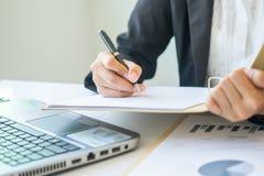 Donna di affari dell'Asia che analizza i grafici di investimento sullo scrittorio Immagine Stock Libera da Diritti