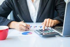 Donna di affari dell'Asia che analizza i grafici di investimento sullo scrittorio Fotografie Stock