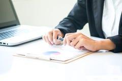 Donna di affari dell'Asia che analizza i grafici di investimento sullo scrittorio Immagine Stock