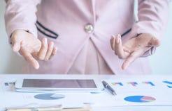 Donna di affari dell'Asia che analizza i grafici di investimento sullo scrittorio Fotografia Stock