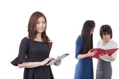 Donna di affari dell'Asia che sta in compressa di uso dell'ufficio, fotografia stock libera da diritti