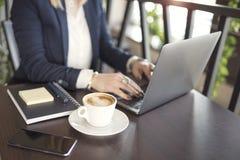 Donna di affari dell'interno con caffè ed il computer portatile sulla tavola di legno immagini stock libere da diritti