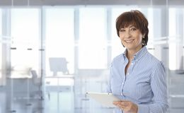 donna di affari dell'Mezzo adulto che per mezzo del computer della compressa Immagini Stock Libere da Diritti