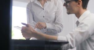 Donna di affari dell'uomo d'affari che analizza i grafici ed i grafici di reddito facendo uso del computer della compressa Analis stock footage