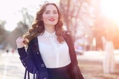 Donna di affari della ragazza in primavera su una passeggiata in un cappotto fotografia stock libera da diritti