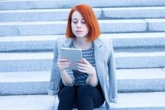 Donna di affari della testarossa che si siede sulle scale che leggono qualcosa con una compressa Fotografia Stock