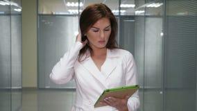 Donna di affari della testarossa in vestito con la compressa che sta nel corridoio dell'ufficio stock footage