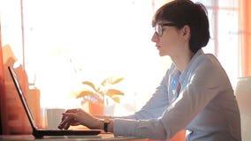 Donna di affari di ambizione che scrive sul suo computer portatile stock footage