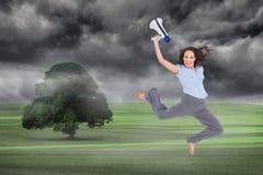 Donna di affari di classe allegra che salta mentre tenendo megafono immagini stock libere da diritti
