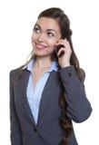 Donna di affari di risata con capelli marroni lunghi al telefono Immagini Stock