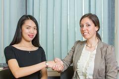 Donna di affari due che stringe le mani dal computer Immagine Stock Libera da Diritti