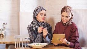 Donna di affari di due musulmani che lavora alla compressa in caffè video d archivio
