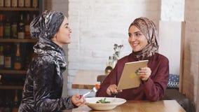 Donna di affari di due musulmani che lavora alla compressa in caffè stock footage