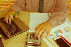 donna di affari e computer portatile di concetto di contabilità di affari con il calcolatore su area di lavoro della tavola Immagine Stock