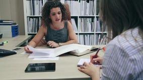 Donna di affari e segretario che lavorano con i documenti in ufficio video d archivio