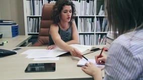 Donna di affari e segretario che lavorano con i documenti in ufficio stock footage