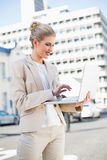 Donna di affari elegante allegra che lavora al computer portatile Immagini Stock Libere da Diritti