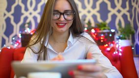 Donna di affari elegante che tiene un computer della compressa in sue mani in caffè video d archivio