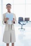 Donna di affari elegante severa che per mezzo della sua compressa Fotografia Stock