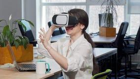 Donna di affari emozionante adorabile che ride allegro, facendo uso della cuffia avricolare di realtà virtuale 3d video d archivio